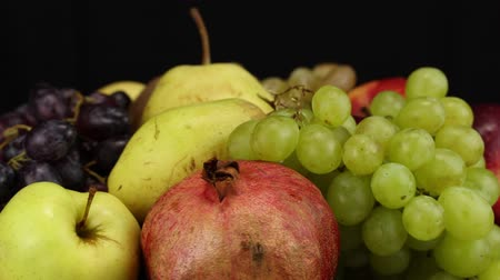 uvas : Green grapes, pomegranate, pear and dark grapes rotate counterclockwise, side view