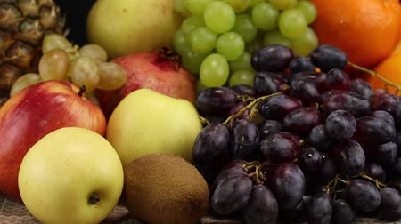 roma : A bunch of different fruits lies on a gray surface on a black background, close-up