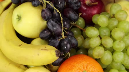 winogrona : Dark grapes, bananas, apples and orange rotate clockwise, top view, close-up Wideo