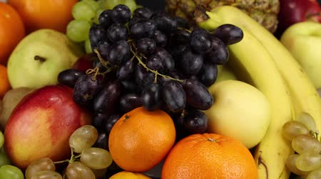 banan : A female hand lays a bunch of dark grapes on a large pile of different fruits Wideo