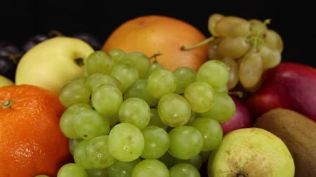 grejpfrut : Grapes, orange, grapefruit and apples rotate clockwise on a black background, side view, close-up