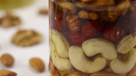 hazelnuts : Glass jar with walnuts, hazelnuts, cashews and almonds in honey on a white surface on a black background, close-up Stock Footage