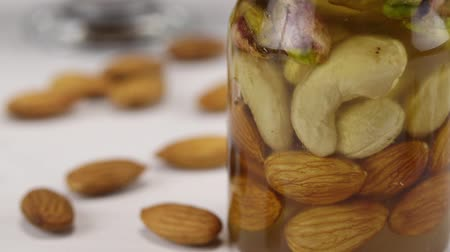 calorias : Focus translation from a glass transparent bowl with almonds to a glass jar with cashew nuts, pistachios and almonds in honey, close-up
