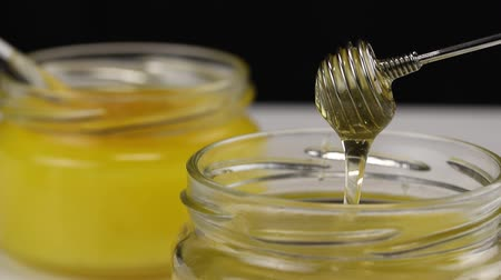 улей : From a metal twisted spoon, honey flows into a glass jar, close-up