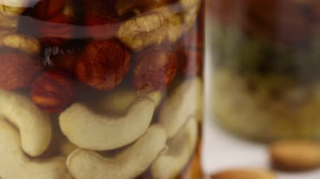 ネクター : Mix of nuts in honey in a glass jar, close-up