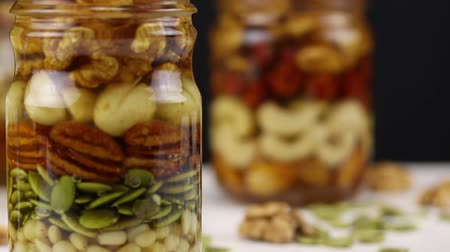 ネクター : The transition from blur to focus on two glass jars with a mixture of nuts, seeds and honey, close-up