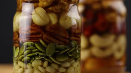 心のこもった : Glass jars with nuts and seeds in honey rotate clockwise, side view, close-up