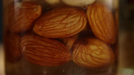 心のこもった : Three glass jars with a mixture of nuts in honey rotate clockwise, side view, very close-up