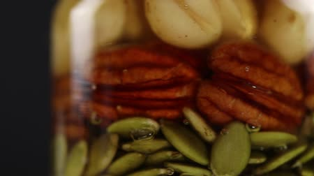 ネクター : Two glass jars with a mixture of nuts and pumpkin seeds in honey rotate clockwise, side view, very close-up