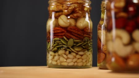 улей : A mixture of nuts and seeds, drenched in honey, in glass jars rotate clockwise on a black background, close-up