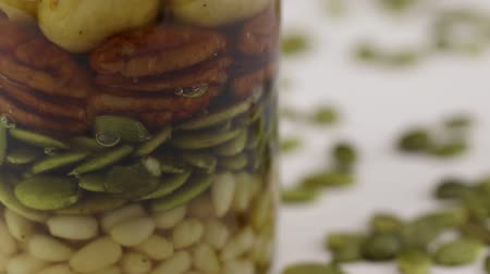 megtöltött : A glass jar filled with a mixture of nuts and seeds and honey, close-up