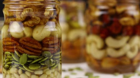 ネクター : Focus shift in turn to each of the three glass jars with a mixture of nuts and honey, close-up