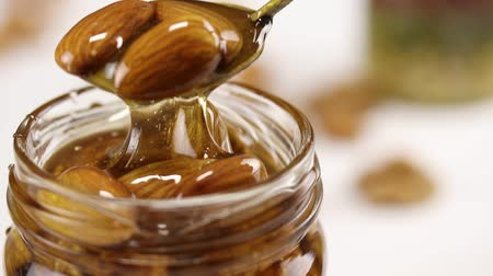 cera : From a glass jar filled with honey and nuts pulled out a metal spoon with almonds in honey Stock Footage