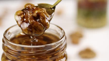 心のこもった : An iron spoon with walnuts in honey is pulled out of a glass jar filled with honey and nuts