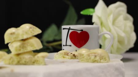 sweetened : White porous chocolate lies on a white surface next to a white mug with a heart logo Stock Footage