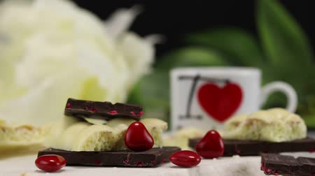 sweetened : White airy chocolate, black chocolate with fruits and heart-shaped candies lie on a white surface against a white flower