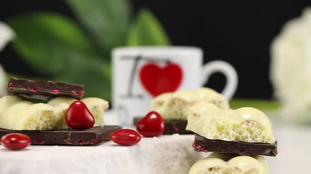 sweetened : White airy chocolate, black chocolate with fruits and heart-shaped candies lie on a piece of white marble on a background of white flowers