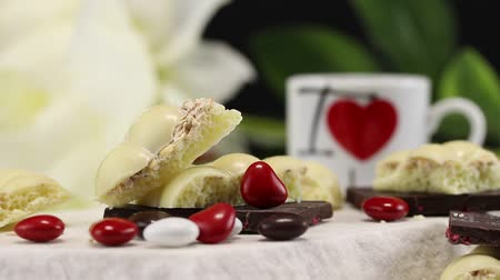 sweetened : White porous chocolate, dark chocolate with fruits and heart-shaped candies lie in the foreground, in the background someone puts a white mug with a heart logo
