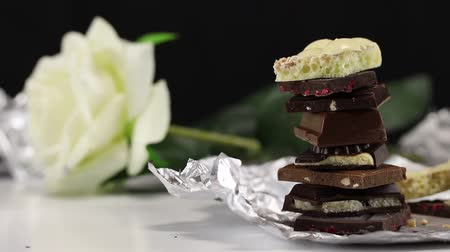 калория : Pieces of different chocolate with different fillings on a foil on a white surface on a flower background