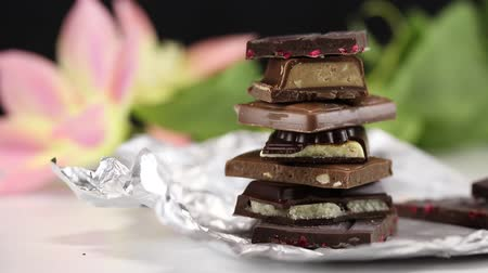 sweetener : Pyramid of pieces of dark chocolate with different fillings on a foil on a background of flowers Stock Footage