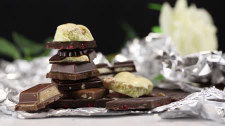 sweetened : Demonstration of pieces of white and dark chocolate from blur to focus Stock Footage