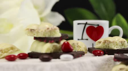 風通しの良い : Pieces of white and dark chocolate are in the foreground, in the background someone is pouring black coffee into a white mug with a heart logo