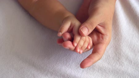 dedo : slow motion of mother touching her baby hand softly between baby sleeping