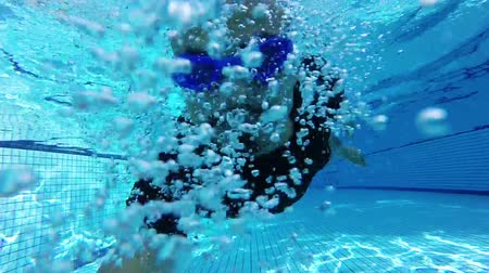 ползком : underwater footage of man swimming. diving in the pool. shot underwater. Asian man has mustaches swimming underwater with blue goggles. Стоковые видеозаписи