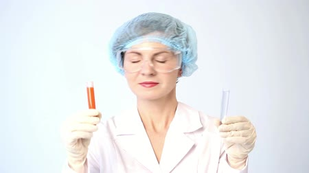 comparar : Female chemist comparing test tubes with chemicals. protective glasses