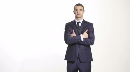 превосходство : body language. man in business suit isolated white background. gestures of arms and hands. posture of superiority. emphasis thumbs. crossed arms