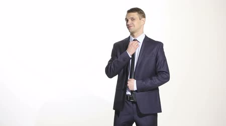 düşünceli : body language. man in business suit isolated on white background. straightens his tie, flirting