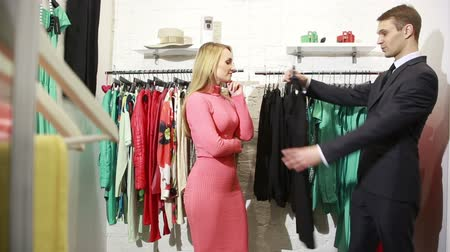 consumismo : Male seller offers women dress. blonde chooses clothes Vídeos