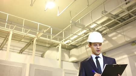 biztonság : man in business suit and helmet. inspects premises. consults with the plan. unhappy with the quality of work