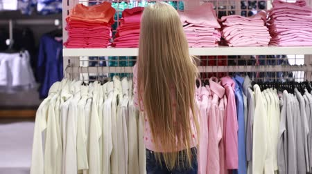носить : Baby girl looking at clothes in fashionable shop Стоковые видеозаписи