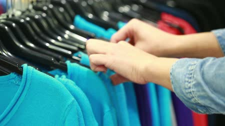 roupas : Buyer chooses a T-shirt in a boutique Stock Footage