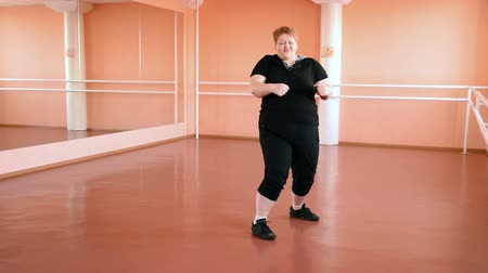 жир : fat girl is engaged in dances in the hall. cheerful plump, gymnastics and dance