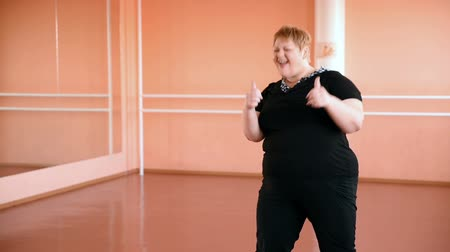xxl : fat girl is engaged in dances in the hall. cheerful plump, gymnastics and dance