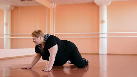 tłuszcz : fat girl is engaged in dances in the hall. cheerful plump, gymnastics and dance