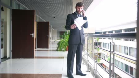 munkahelyek : Mature Businessman Working With Papers And Cellphone At Workplace Stock mozgókép