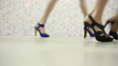 pięta : Female legs walking in high heel shoes.