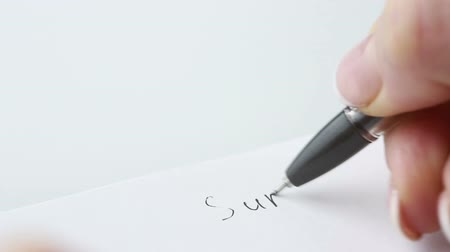 synopsis : Female hands holding pen and blank paper sheets with copyspace on table. He writes the word summary