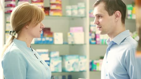 dispensary : Pharmacist woman offers the visitor a cure at the chemists shop