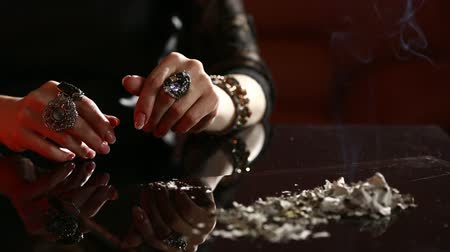 palmist : Witch - fortune teller reading fortune close up. smoking ash