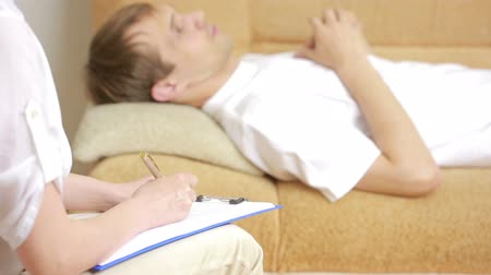 counselling : man lying on sofa and talking with psychologist Stock Footage