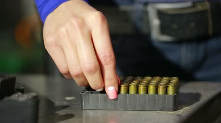 charges : young woman with the gun. indoor shooting range. charges cartridges in the gun Stock Footage