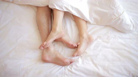 над : a man and a woman in bed. male and female legs top view, white linens