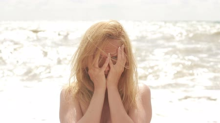 cabelos grisalhos : Sad woman crying during storm on the beach. hair fluttering in the wind