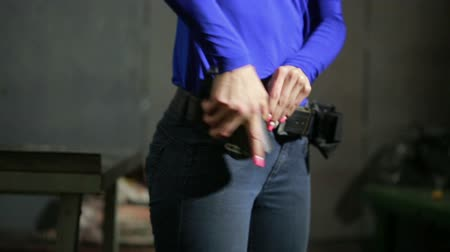 marksman : young woman with the gun on an indoor shooting range. collect gun