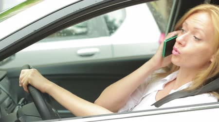 telefon : Frustrated woman stuck in a traffic jam. girl talking on the phone in the car