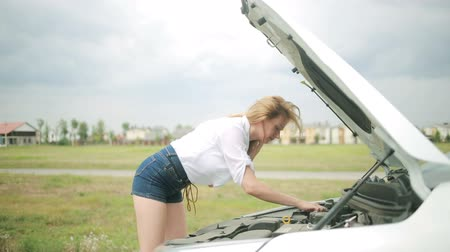 pneus : woman opens the hood Broken car. girl looks at a damaged engine. Stock Footage